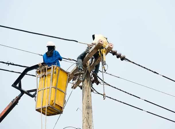 Electrical utility workers repairing problem with power line on