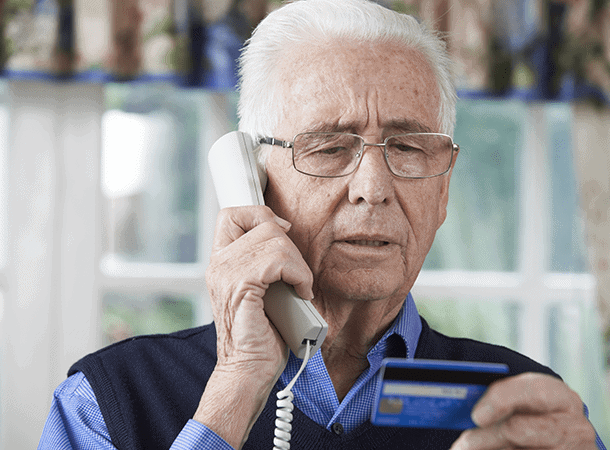 Older man on the phone reading his Credit Card