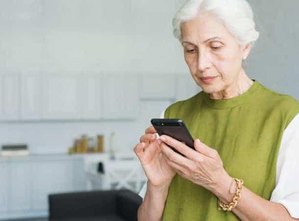 portrait senior woman texting cell phone home
